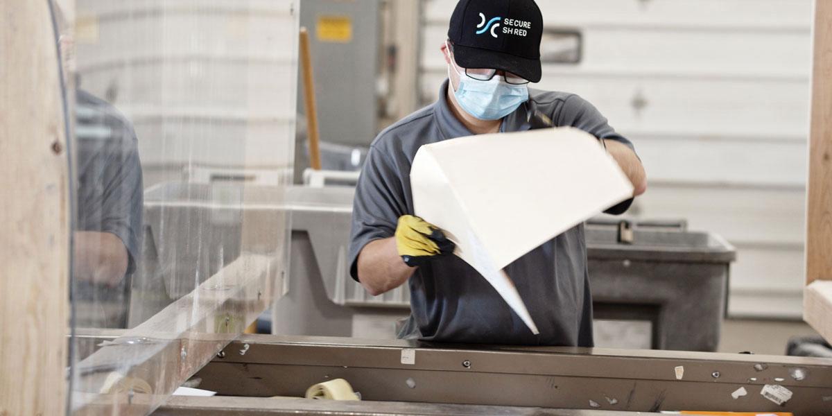 A SecureShred employee seperating paper for shredding.