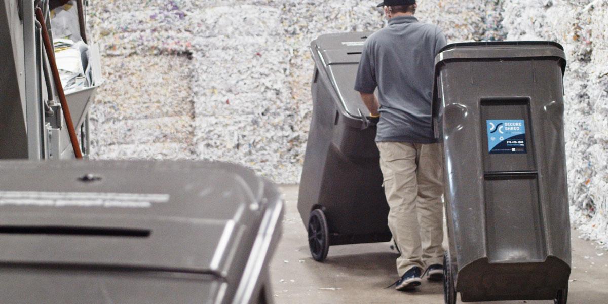 An employee moving two garbage bins